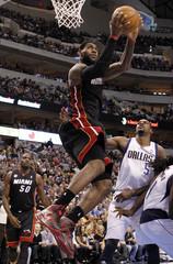 Miami Heat forward LeBron James shoots as Dallas Mavericks center Bernard James is near during their NBA basketball game in Dallas, Texas