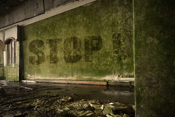 text stop on the dirty old wall in an abandoned ruined house