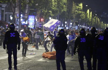 Police confront youths on the Champs Elysee after Portugal's Euro 2016 win in Paris