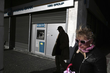 People walk outside a branch of National Bank of Greece in Athens