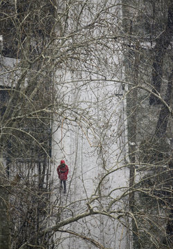 A woman walks in the snow at a residential community in central Beijing