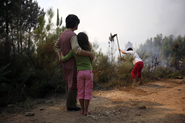 A woman and her child watch as a volunteer fights against a forest fire near Mengualde