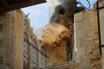 An excavator tears down the Saint-Pierre-aux-Liens church in the village of Geste, western France, western France