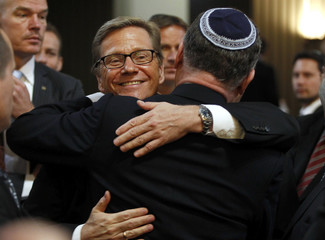 German Foreign Minister Westerwelle embraces World Jewish Congress President Lauder during ordination ceremony at Roonstrasse Synagogue in Cologne
