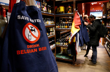 """A sign on an apron reading """"Save water drink Belgian beer"""" is pictured in a shop in central Brussels"""