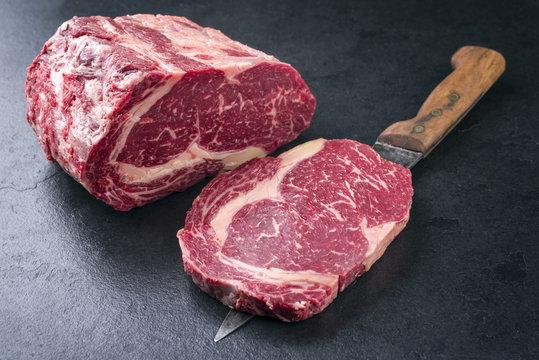 Raw dry aged Kobe Entrecote Steak as close-up on a slate .
