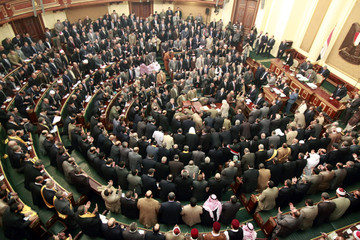 Members of the parliament stand and pray during the first Egyptian parliament session after the revolution that ousted former President Hosni Mubarak, in Cairo