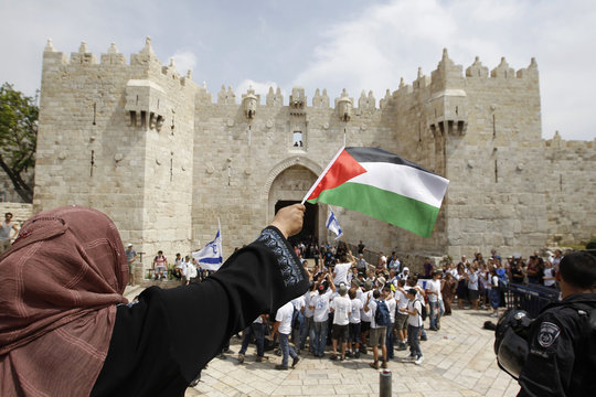 A Palestinian woman waves a Palestinian flag as Israeli youths dance in front of the Damascus Gate in Jerusalem's Old City