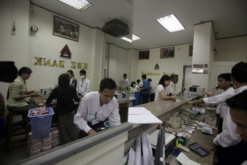 Staff members serve customers at Kanbawza Bank in Yangon