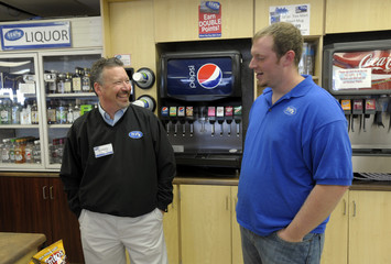 Baron Hartell, son of the owner of a Trex Mart gas station, where one of two winning tickets in a $587.5 million Powerball lottery was sold at, talks with the company's GM Kenny Gilbert in Dearborn, Missouri