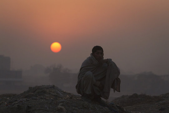 A man squats down silhouetted against the setting sun as he looks on at children playing in the outskirts of Islamabad