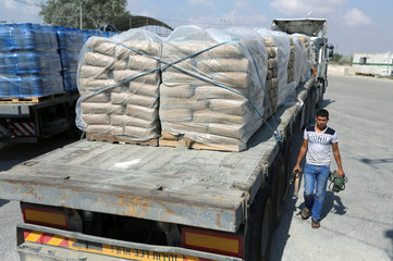 A Palestinian walks next to a truck loaded with bags of cement at the Kerem Shalom crossing between Israel and southern Gaza Strip