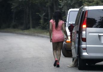 Prostitutes wait for customers along a road of the Bois de Boulogne in Paris