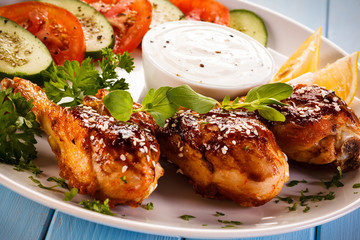 Grilled chicken drumstick on wooden table