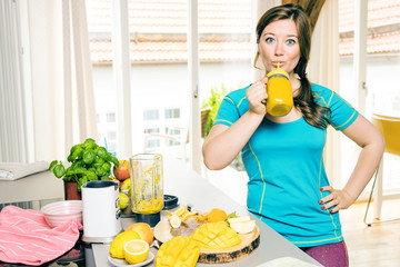 Sportliche frau in der küche (smoothie mixen)