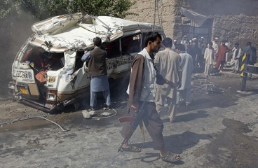 Afghan villagers stand next to a civilian bus that was hit by a remote-controlled bomb, in the Paghman district of Kabul