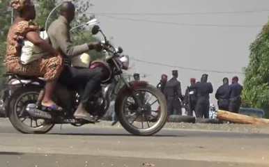 A still image from video thay shows people riding past on a motorbike looking at soldiers standing at a checkpoint in Bouake