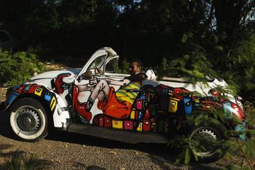 Art collector Andrei de Lima drives his 1972 Volkswagen Beetle decorated with graffiti depicting a hillside favela in Rio de Janeiro