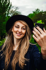Cute blonde in hat posing in front of phone