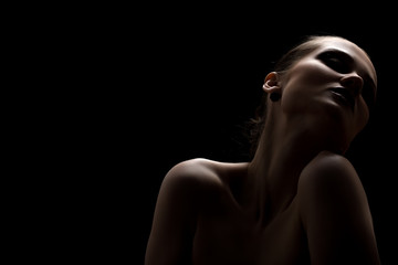 beautiful topless woman with closed eyes on black background