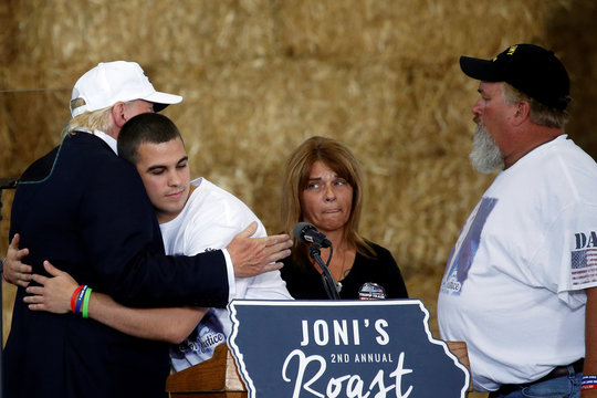 "Republican nominee Donald Trump hugs Scott Root as his mother Michelle Root and father Scott Bernhardt, the family of Sarah Root who died in a DUI car accident, watch on stage at ""Joni's Roast and Ride"" in Des Moines"