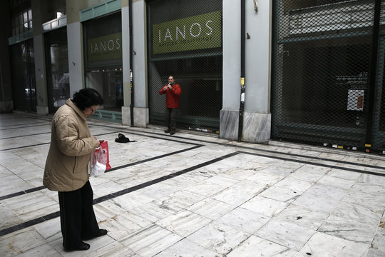 A woman searches her wallet as a street musician performs in a shopping arcade, with mostly shops closed in the last four years of the Greek financial crisis, in central Athens