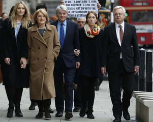 Andrew Mitchell (C), Britain's former Conservative Party chief whip, arrives at the Royal Courts of Justice with his wife Sharon Bennett (2nd L), and Conservative Party member of parliament David Davis in London