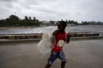 A boy walks along a pier ahead of Hurricane Matthew in Les Cayes, Haiti