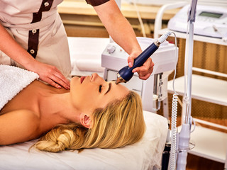 Ultrasonic facial treatment on ultrasound face machine. Woman has electric lift massage spa salon. Stimulation muscles by professional equipment microcurrent therapy. Modern methods of rejuvenation.