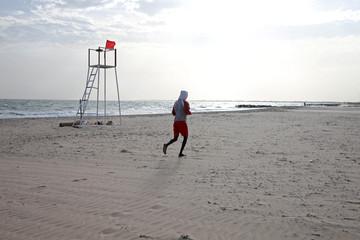 A man jogs on the beach in Bakau