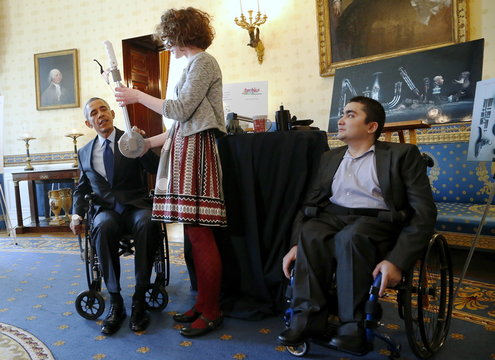 Obama looks at a lever-style wheelchair extensive designed by Reed as he plays host to the 2015 White House Science Fair at the White House in Washington