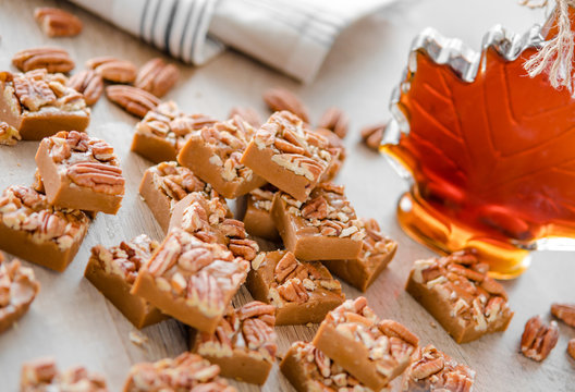 Delicious maple fudge with pecan and maple syrop on the  background
