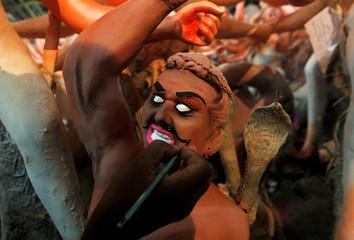 An artisan paints an idol of mythological demon Mahisasura ahead of the Durga Puja festival, in Allahabad