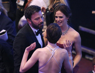 Actress Anne Hathaway talks to director Ben Affleck at the 85th Academy Awards in Hollywood