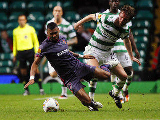 Stade Rennes' M'Villa falls to the ground from the tackle of Celtic's McCourt during their Europa League Group I soccer match at Celtic Park stadium in Glasgow