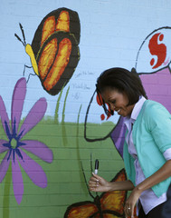 U.S. first lady Michelle Obama smiles after signing a painting of a butterfly at the Marie Reed learning center in Washington