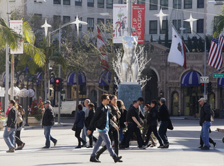 Tourists cross Rodeo Drive as Christmas decorations are pictured in the background in Beverly Hills