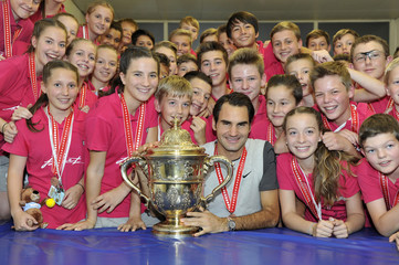 Switzerland's Federer and tournament's ball boys and girls pose with the trophy after he won his final match at the Swiss Indoors ATP tennis tournament in Basel