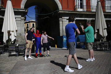 Tourists get their picture taken with a street performer dressed as Spiderman at the Plaza Mayor Square in central Madrid