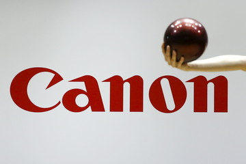 A gymnast performs in front of the Canon brand logo at the Canon stall at CP+ camera and photo trade fair in Yokohama