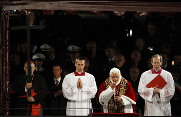 Cardinal Agostino Vallini holds the cross as Pope Benedict XVI leads the Via Crucis (Way of the Cross) procession at the Colosseum in downtown Rome