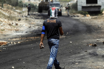 A stone-throwing Palestinian protester walks during clashes with Israeli soldiers near Nablus