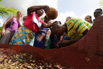 Rita Ravenberg pours sacred water containing herbs and flowers on people during a New Year's Eve ritual bath in Paramaribo