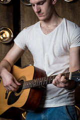Guitarist, music. A young man plays an acoustic guitar on a background with lights behind him. Vertical frame