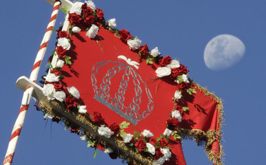 "A ""Holy Spirit"" flag is seen with the moon in the background during the ""Cavalhadas"" festival in Pirenopolis"