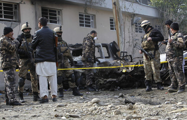Afghan security personnel investigate at the site of a suicide attack in Sroubi district