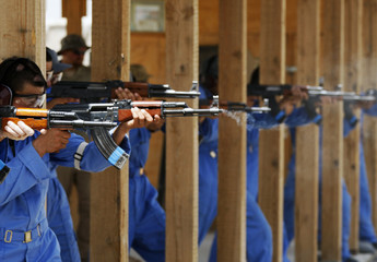 Afghan policemen shoot with their Kalashnikovs during training with Canadian police instructors at the range in Camp Nathan Smith in Kandahar City