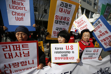 Activists hold banners bearing messages to wish U.S. ambassador to South Korea Mark Lippert a speedy recovery, in Seoul