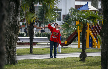 Fan of Russia takes pictures near palm trees on a warm day in Adler during the 2014 Sochi Winter Olympics