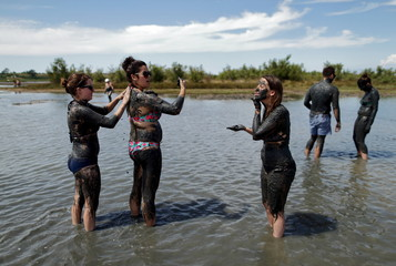 Girls smear each other with mud that is believed to be curative at Queen's beach in Nin, south Croatia